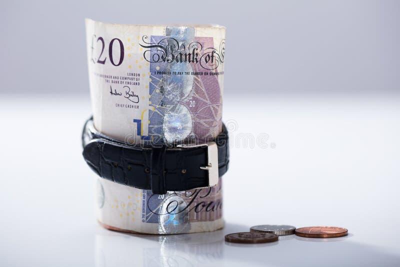 Rodado encima de veinte libras de nota de la moneda dentro del reloj fotos de archivo