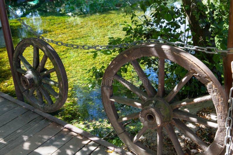 Rodas de vagão de madeira velhas ao lado do lago imagens de stock royalty free