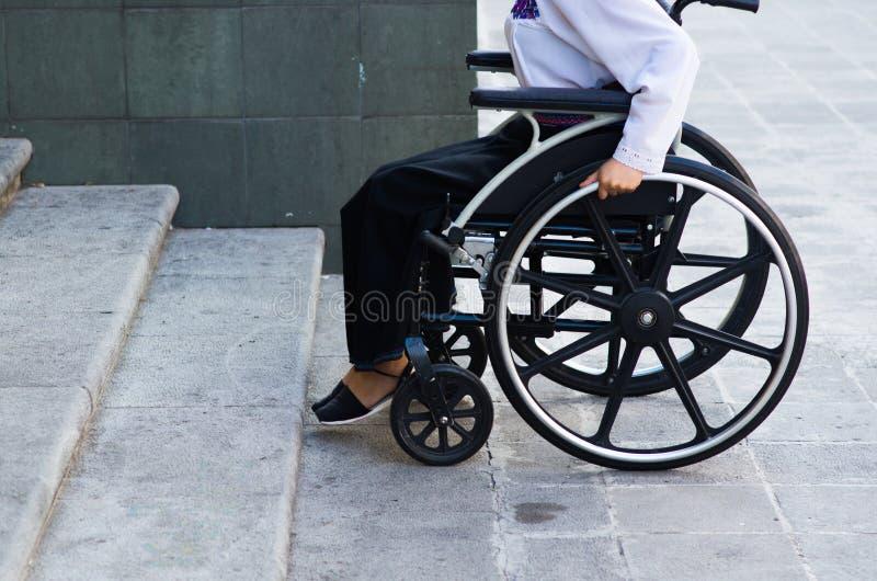 Rodas do close up da cadeira de rodas com a mulher que senta-se nele, conceito deficiente físico fotografia de stock royalty free