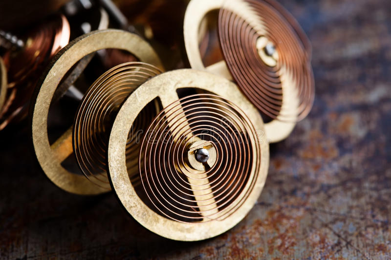 Rodas do maquinismo de relojoaria do vintage com mecanismo da mola O bronze alinha rodas denteadas no fundo oxidado, profundidade imagens de stock