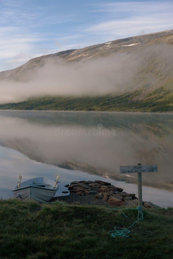 Roddbåt på en lugna sjö arkivfoto