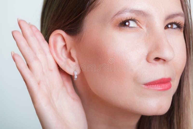 Roddelmeisje die met hand aan oor afluisteren royalty-vrije stock foto
