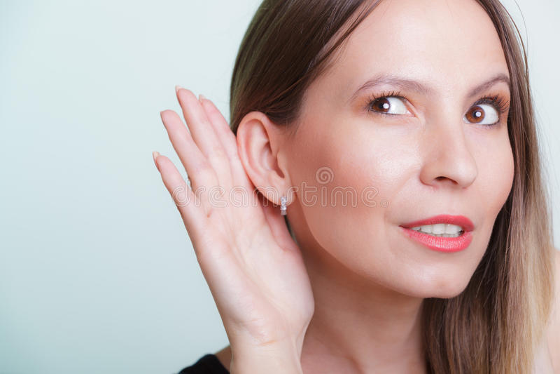 Roddelmeisje die met hand aan oor afluisteren stock foto's