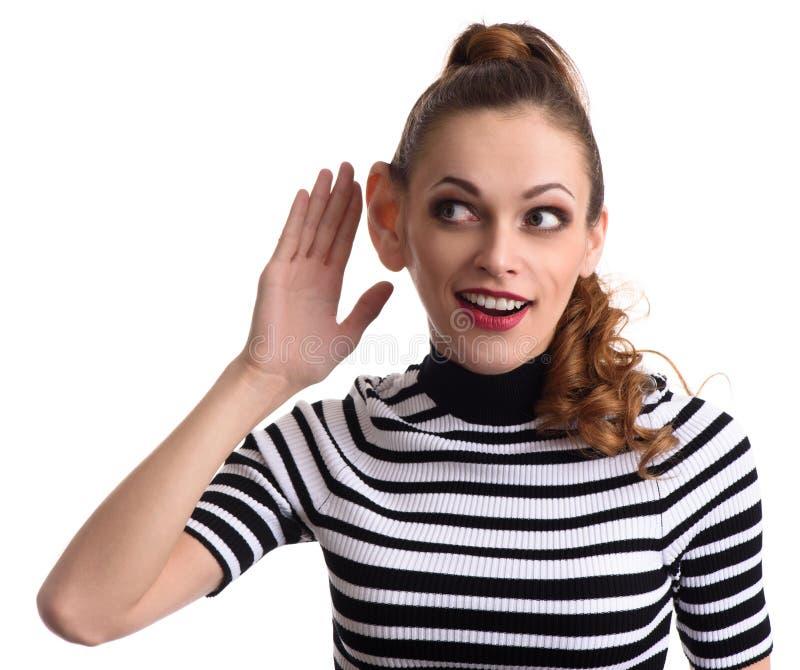 Roddelmeisje die met hand aan oor afluisteren stock foto