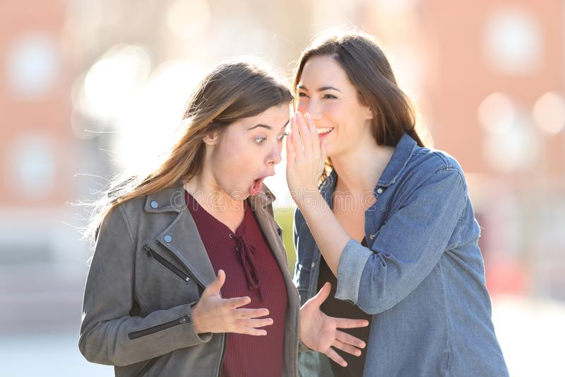 Roddelmeisjes die op oor een geheim in de straat fluisteren stock foto