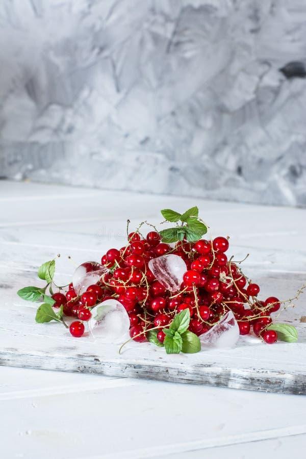Rode aalbes met ijs en groene bladeren op witte houten achtergrond stilleven van voedsel Kubussen van ijs met bessen stock afbeeldingen