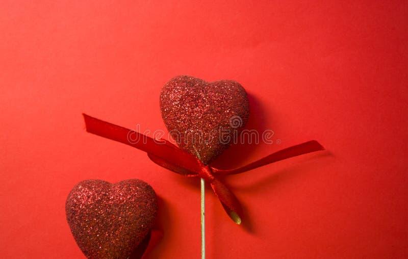 Rode achtergrond St de Dag van de valentijnskaart ` s Rode harten in lovertjes en met bogen Liefde romanticism De plaats voor een royalty-vrije stock foto