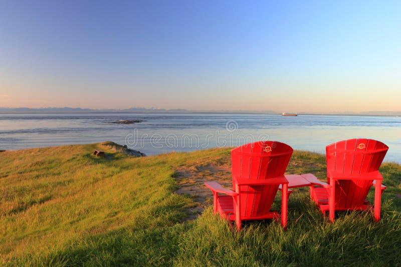 Rode Adirondack-Stoelen op het Punt van het Oosten, Saturna Eiland, het Nationale Park van Golfeilanden, Brits Colombia royalty-vrije stock foto's