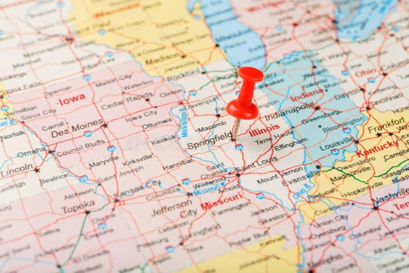 Rode administratieve naald op een kaart van de V.S., Illinois en hoofdspringfield Sluit omhoog kaart van Illinois met rode kopspi stock foto's