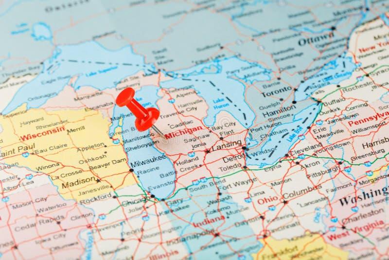 Rode administratieve naald op een kaart van de V.S., Michigan en hoofdlansing Sluit omhoog kaart van Michigan met rode kopspijker stock foto's