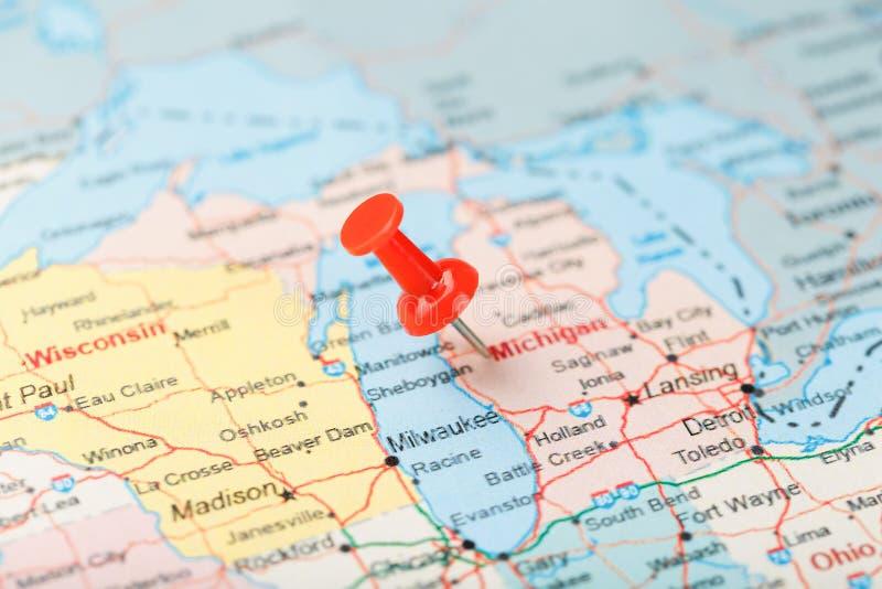 Rode administratieve naald op een kaart van de V.S., Michigan en hoofdlansing Sluit omhoog kaart van Michigan met rode kopspijker stock foto
