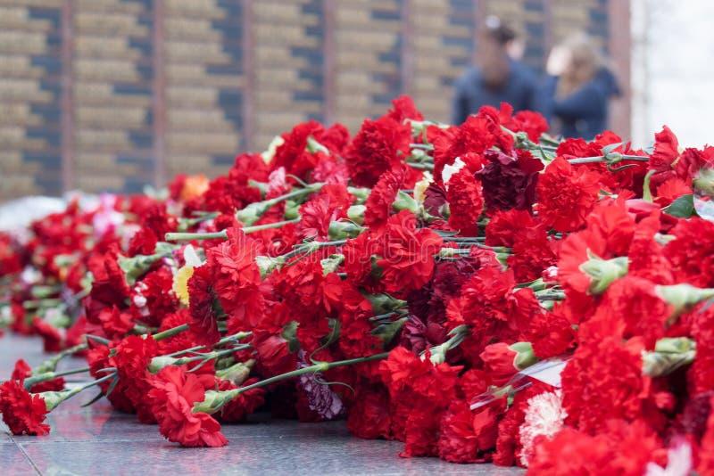 Rode anjerbloemen op een herdenkings marmeren raad Herdenkings gevallen militairen in de Wereldoorlog II royalty-vrije stock foto