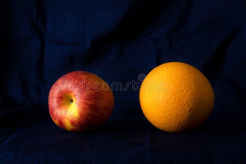 Rode appel en het oranje klassieke fruit van het stillevenvoedsel met de donkere achtergrond van de zijde blauwe stof royalty-vrije stock fotografie