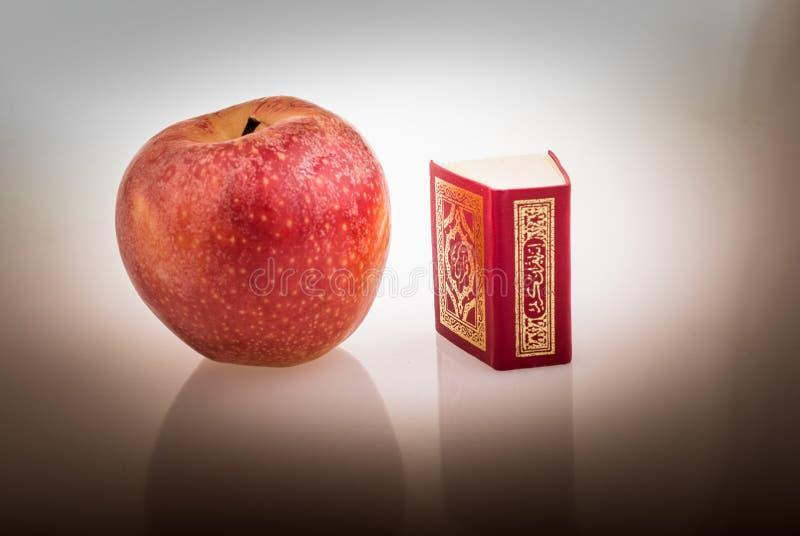 Rode appel en Islamitisch Heilig Boek Quran royalty-vrije stock fotografie