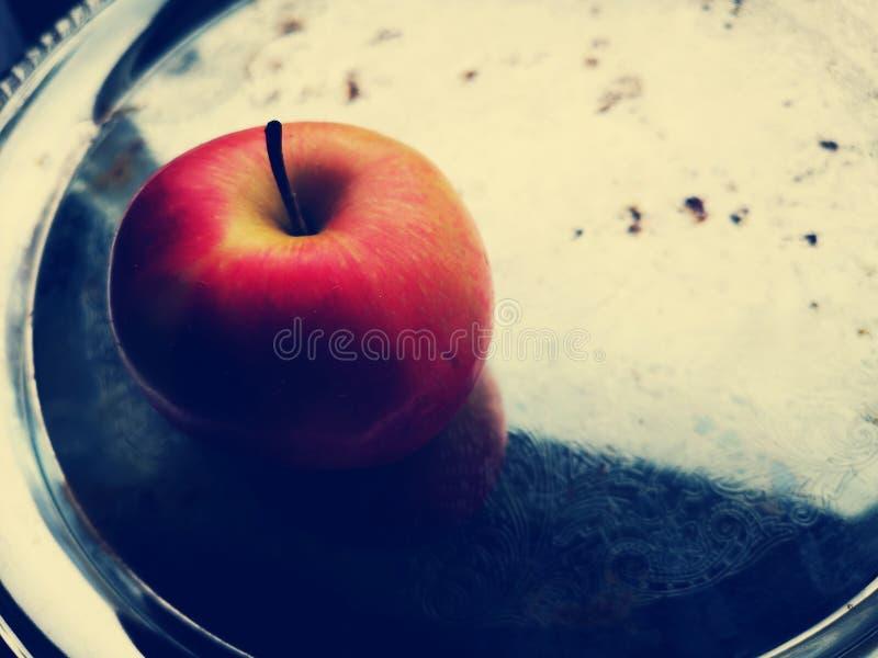 Rode appel op een oud metaaldienblad stock foto's