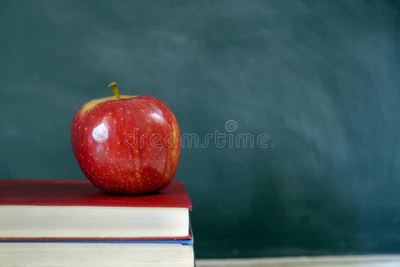 Rode appel op schoolhandboek stock afbeelding