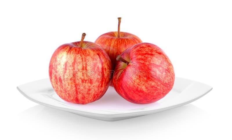 Rode appel in witte plaat op witte achtergrond stock foto's