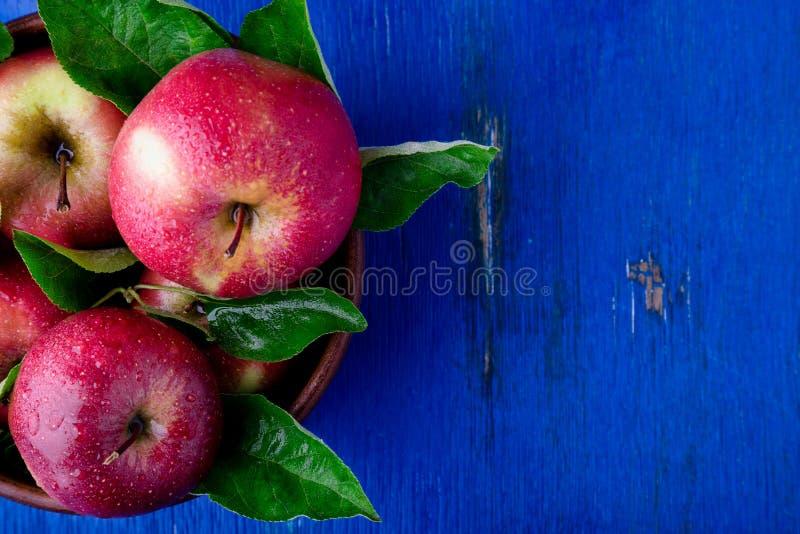 Rode appelen in bruine kom op blauwe houten achtergrond Hoogste mening De ruimte van het exemplaar royalty-vrije stock afbeelding
