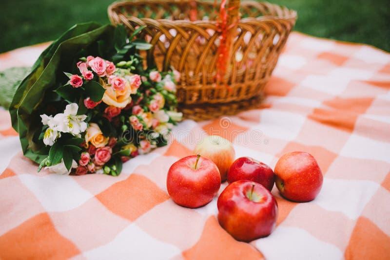 Rode appelen en trouwringen op een plaiddeken dichtbij de mand stock afbeelding