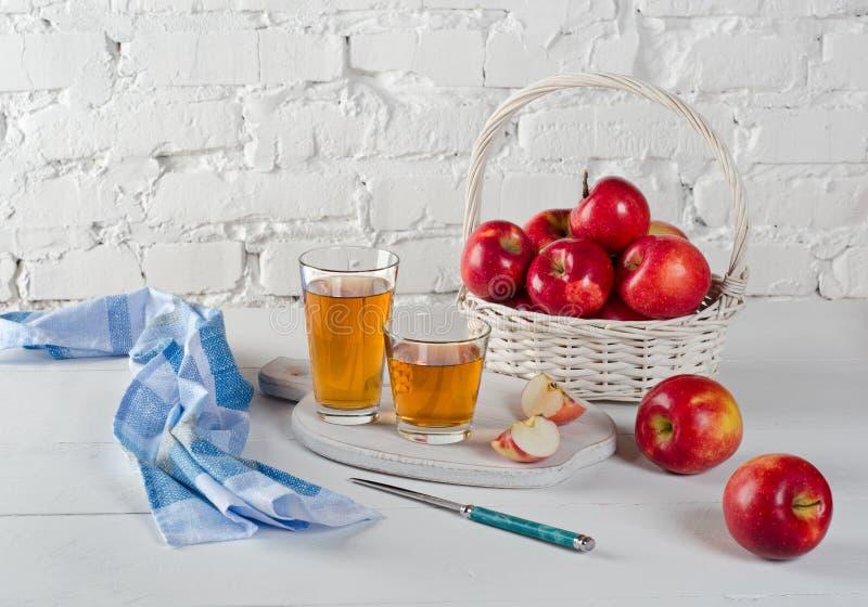 Rode appelen, sap in glazen, blauw servet en een mes royalty-vrije stock foto