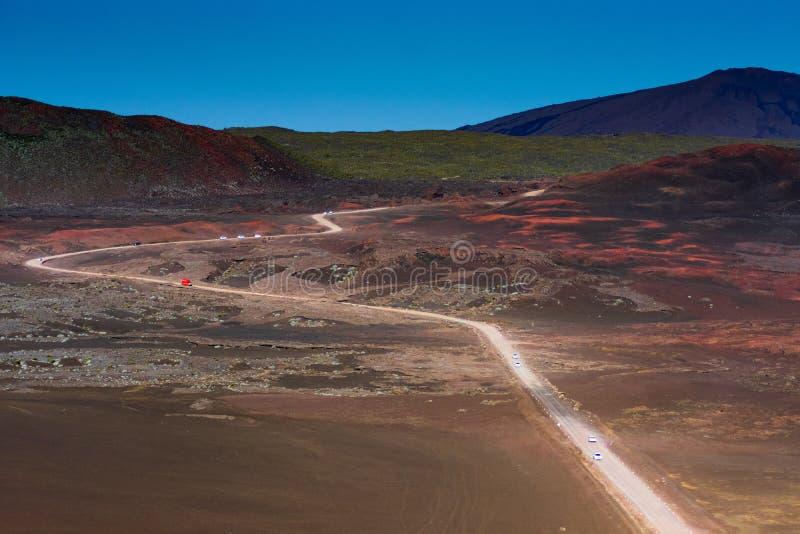 Rode auto op weg in droog landschap die tot de vulkaan van het Bijeenkomsteiland leiden stock fotografie
