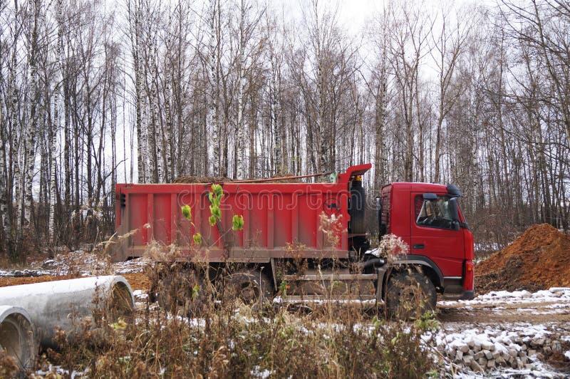 Rode auto - stortplaatsvrachtwagen op het werk stock fotografie