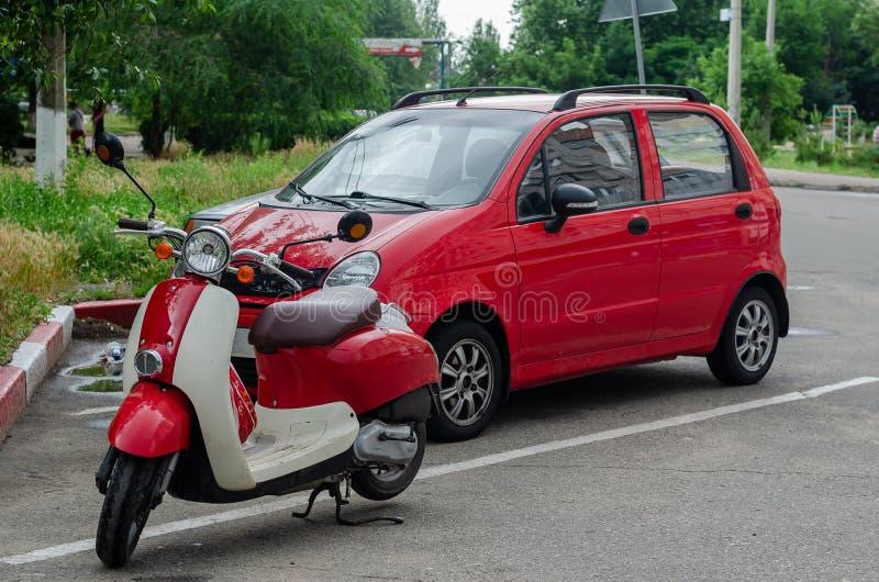 Rode autoped in de retro stijl in het parkeerterrein op de achtergrond van een kleine rode auto stock afbeelding