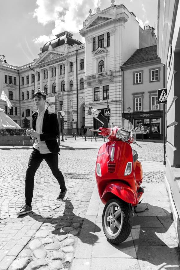 Rode autoped in zwart-witte stedelijke scène stock fotografie