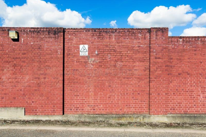 Rode Bakstenen muur met een Waarschuwingsbord stock afbeeldingen