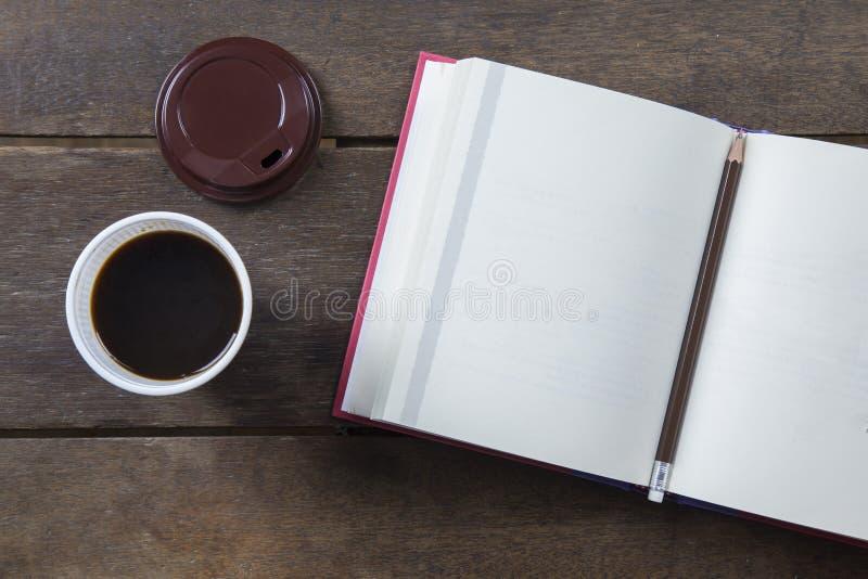 Rode behandelde geopende boek blanco pagina met potlood en zwarte koffie stock afbeelding