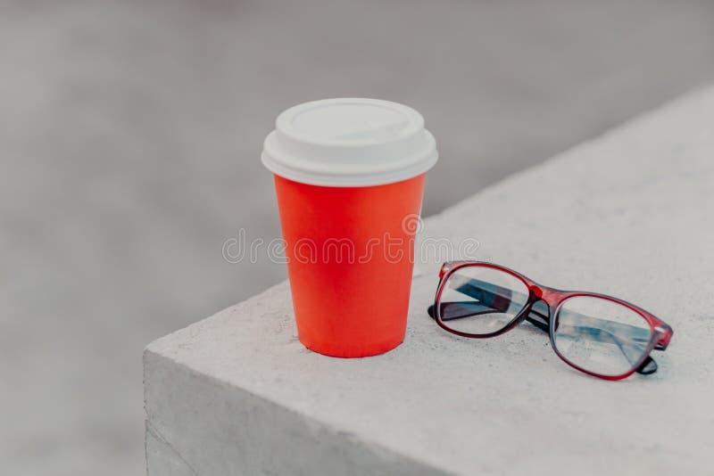 Rode beschikbare kop van hete drank op witte concrete muur, optische glazen dichtbij Meeneemkoffie in document container Geen men royalty-vrije stock afbeeldingen