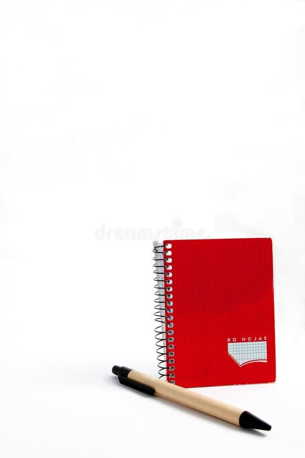 Rode blocnote en pen stock afbeeldingen