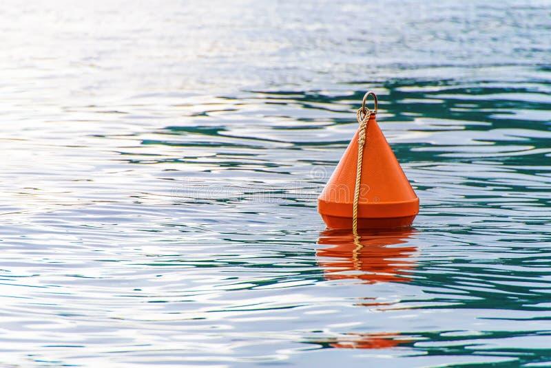 Rode boei op de overzeese golven stock afbeelding