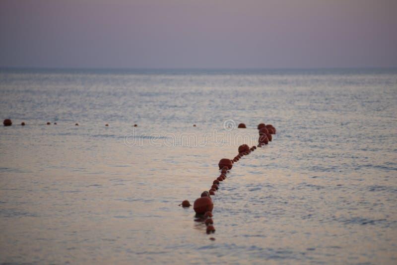 Rode boeien in het overzees op het strand in de avond bij zonsondergang stock foto