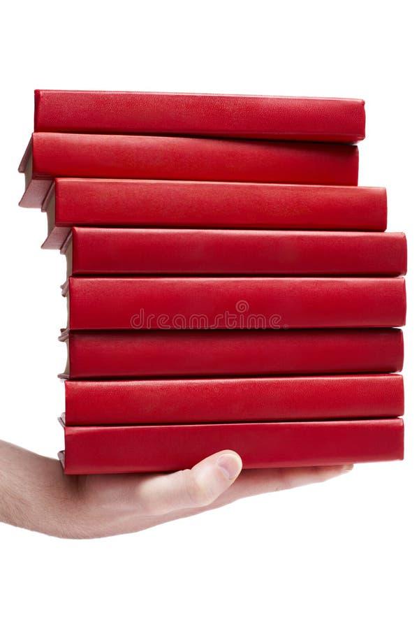 Rode boeken in een hand royalty-vrije stock fotografie