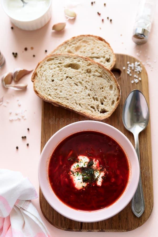 Rode borschtsoep in roze kom met zure room, brood, knoflook en kruiden op roze achtergrond Hoogste mening Vlak leg royalty-vrije stock foto's