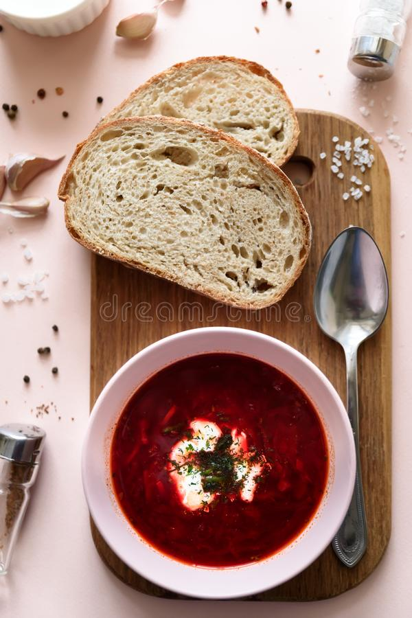 Rode borschtsoep in roze kom met zure room, brood, knoflook en kruiden op roze achtergrond Hoogste mening Vlak leg stock foto