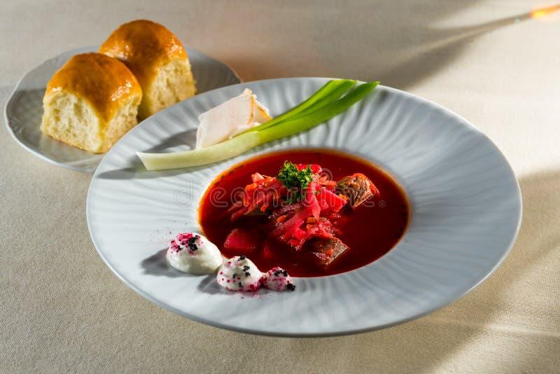 Rode borsjt met zure room en pampushkas en reuzel met uien op een plaat royalty-vrije stock fotografie