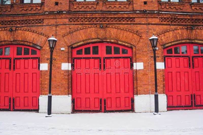 Rode Brandweerkazernedeuren bij de rode bakstenen muurbouw stock foto