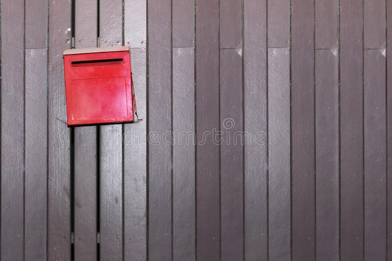 Rode brievenbus op oude houten muur stock afbeeldingen