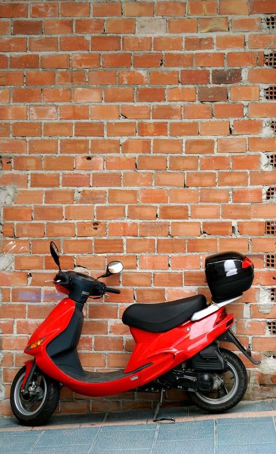 Rode bromfiets of motor die of tegen een bakstenen muur rusten leunen. royalty-vrije stock afbeeldingen