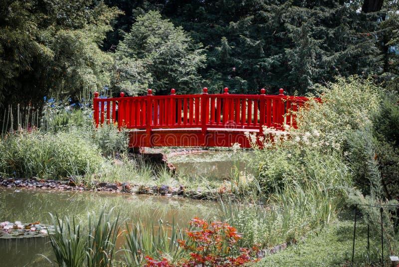 Rode brug over een kleine die stroom door installaties wordt omringd stock foto's