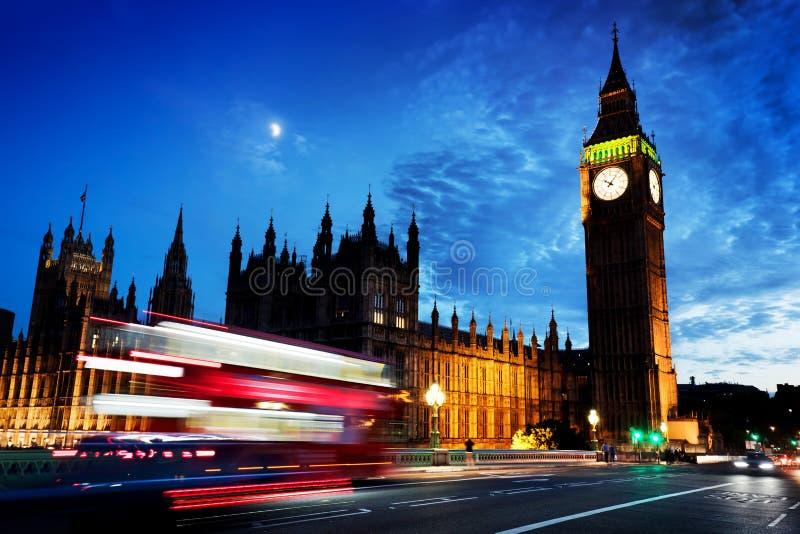 Rode bus, Big Ben en het Paleis van Westminster in Londen, het UK bij nacht Maan het glanzen stock foto