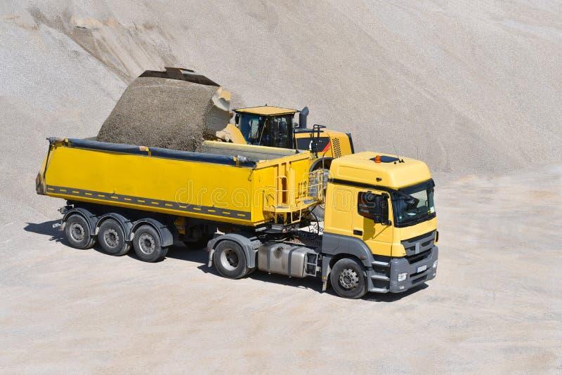 Rode cargas do carregador um caminhão com areia em um poço de cascalho fotografia de stock royalty free