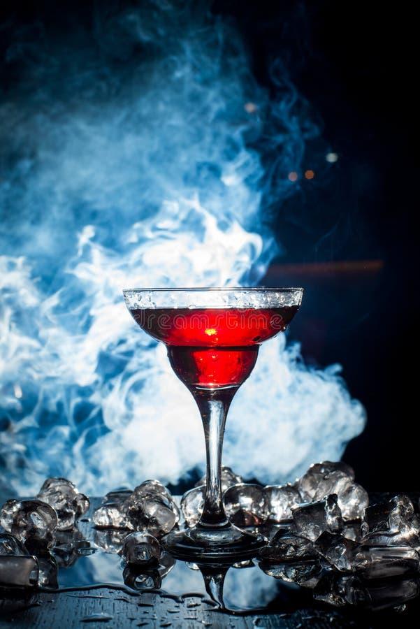 Rode cocktail met ijsdamp, blauwe achtergrond royalty-vrije stock afbeeldingen