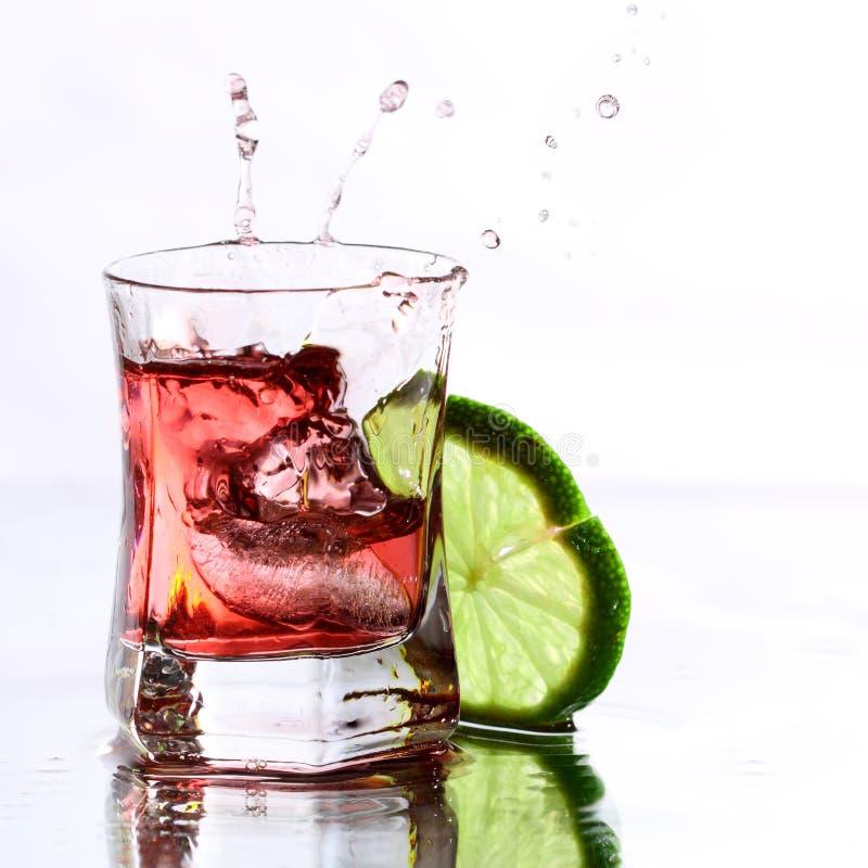 Rode cocktail met kalk op wit stock afbeeldingen