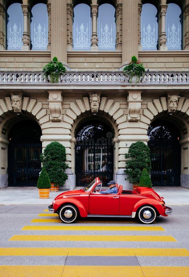 Rode convertibele de looppaspas van de keverauto door boogpoorten van Zwitserse Parli stock foto