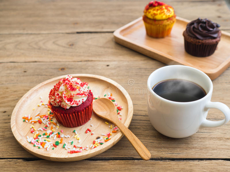 Rode cupcakes gezet op een sferische houten plaat Naast van cupcake hebben witte koffiemok royalty-vrije stock foto