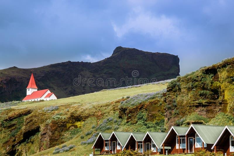 Rode dakkerk op de heuvel, met de zomerplattelandshuisjes in foregro stock afbeeldingen