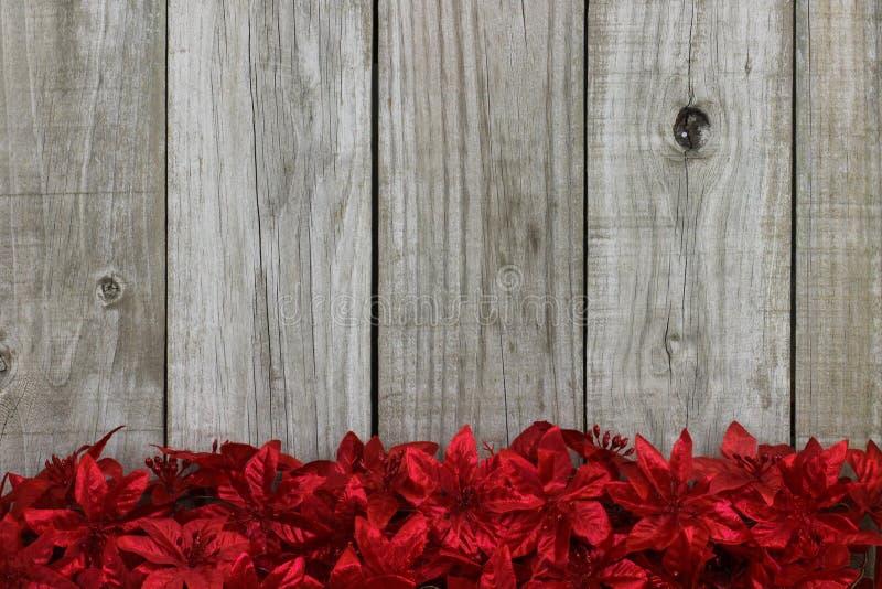 Rode de bloemgrens van de Kerstmisslinger tegen rustieke antieke houten achtergrond stock fotografie